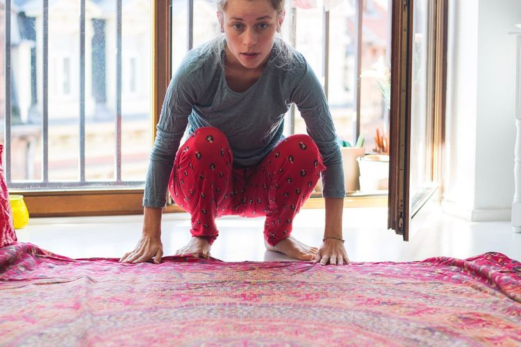 Young Woman Crouching With Fabric At Home