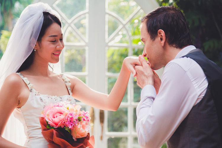 Married couple holding bouquet sitting outdoors