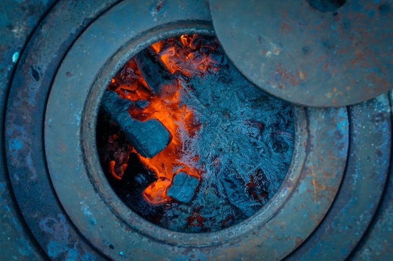 Wintertime Charcoal Fire Burning Flame Metal High Angle View Close-up No People Heat - Temperature Outdoors Metal Industry Industry Day