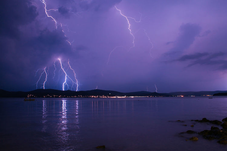 Scenic view of lake at night during storm