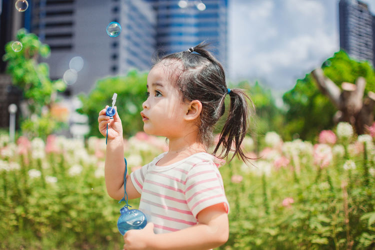 Girl blowing bubbles by flowers at park