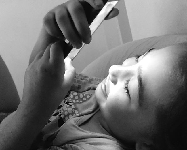 8707940228ca Little girl using the phone for fun Smile Elementary Age Black And White  Photography Black &