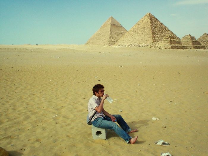 Man sitting on block drinking water against great pyramid of giza
