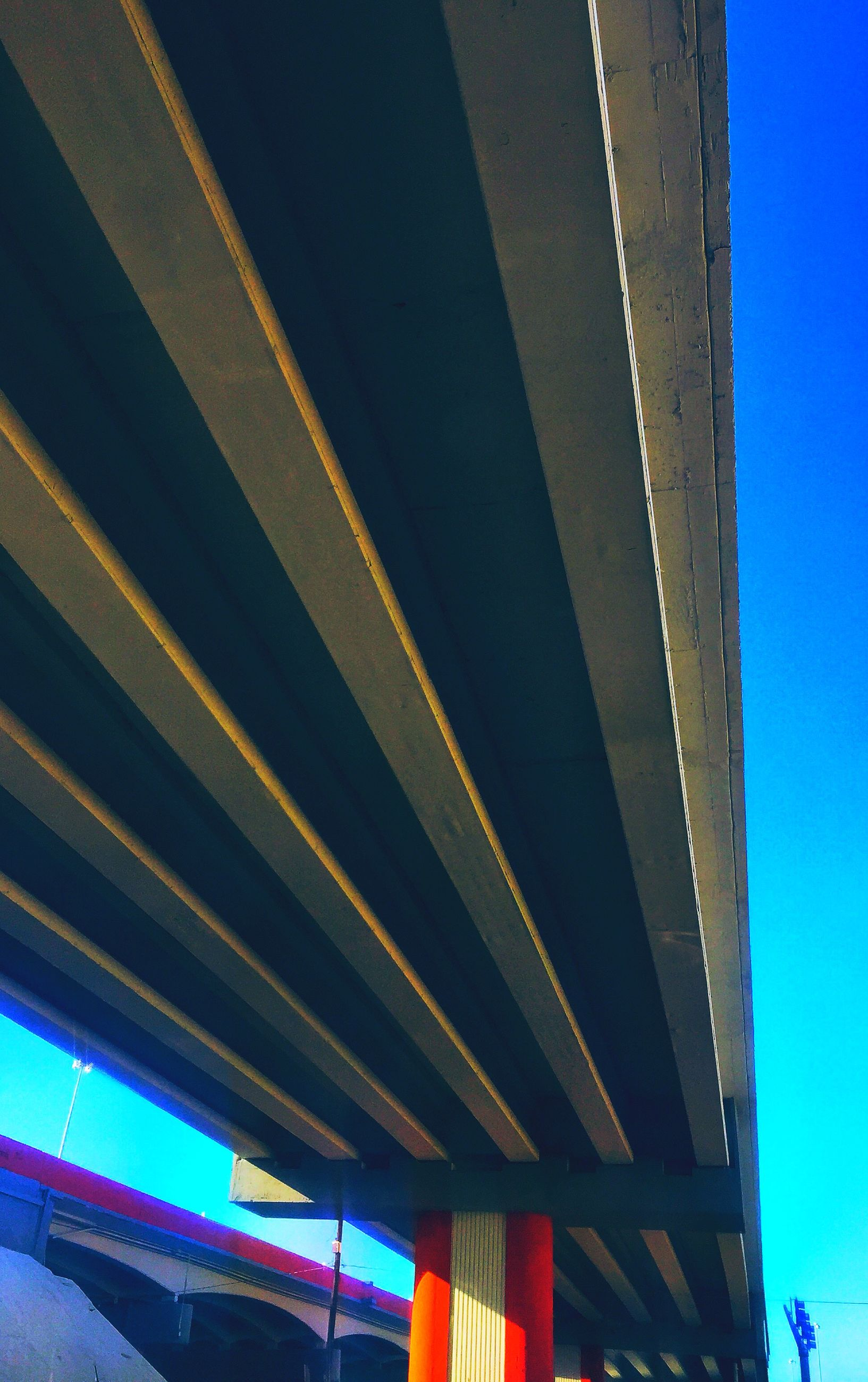 low angle view, built structure, architecture, blue, clear sky, connection, bridge - man made structure, illuminated, engineering, architectural column, copy space, building exterior, no people, outdoors, support, transportation, ceiling, sky, column, bridge