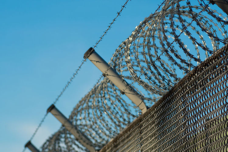 Low angle view of razor wire fence against sky