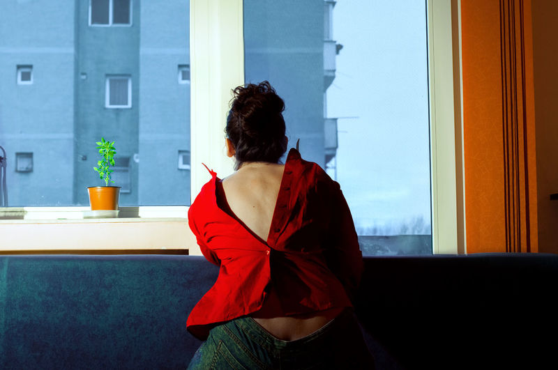 Rear view of woman wearing button down shirt while standing by window at home