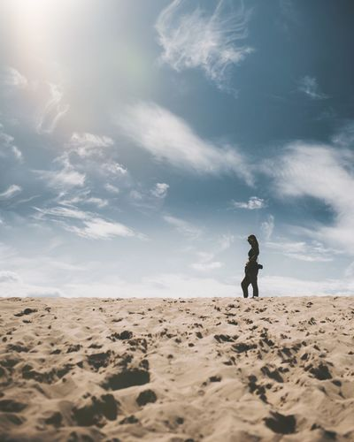 Full length of man on sand at beach against sky