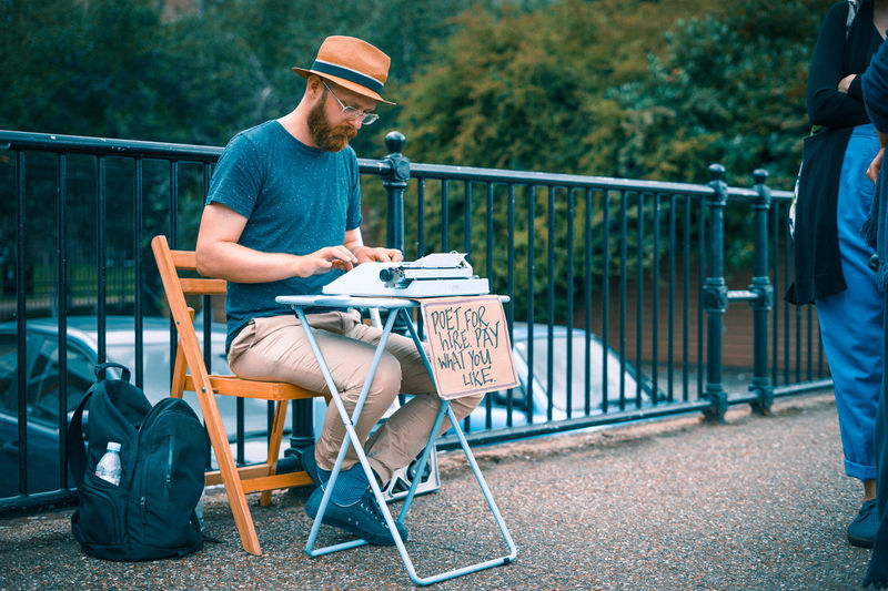 Hat Mobility In Mega Cities River Thames Adult Adults Only Bearded Casual Clothing City Day Full Length Men Mobility One Person Only Men Outdoors People Poem Poet Poetry Railing River Bank  Sitting T-shirt Wooden Chair Young Adult