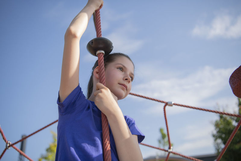 Low angle view of girl playing on jungle gym