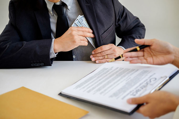 Cropped hands of man giving contract papers for signing to businessman