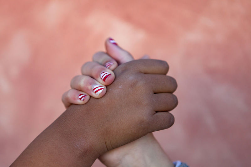 Close-up of girls holding hands