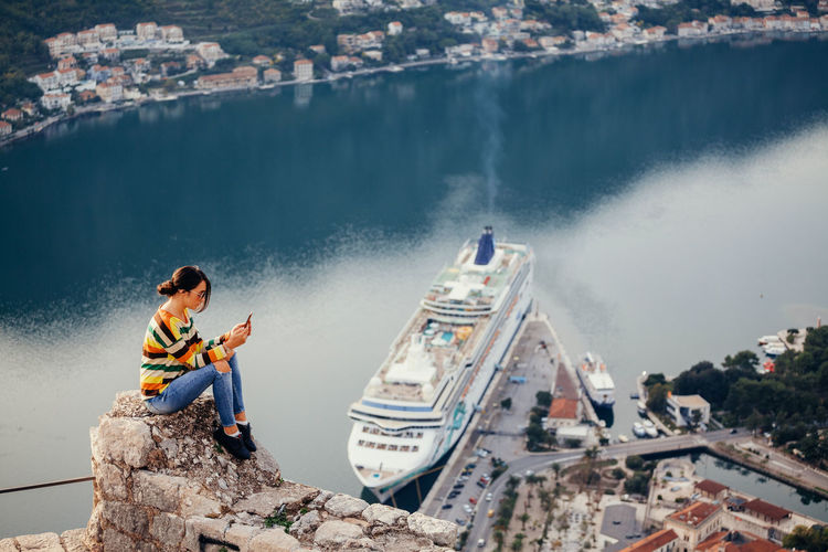 woman travel cruise chip and using phone high angle view. Kotor Bay view Authentic Moments EyeEm Best Shots Panoramic Relaxing Sitting Travel Woman Adult Adventure Aerial View Bay Casual Clothing Chatting Communication Cruise High Angle View Montenegro One Person Outdoors Picturesque Sexygirl Smart Phone Sunglasses