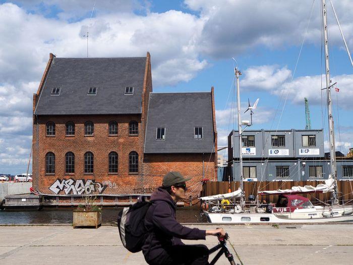 Man in boat against building in city against sky