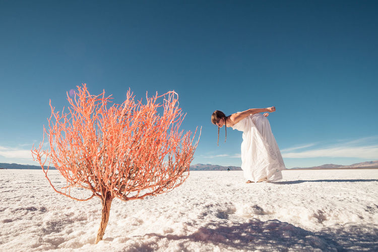 Woman looking at bare tree while bending on snowy field