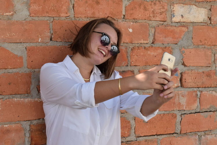 Young woman using phone while standing against brick wall