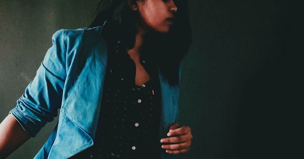 Midsection of woman wearing jacket standing against wall