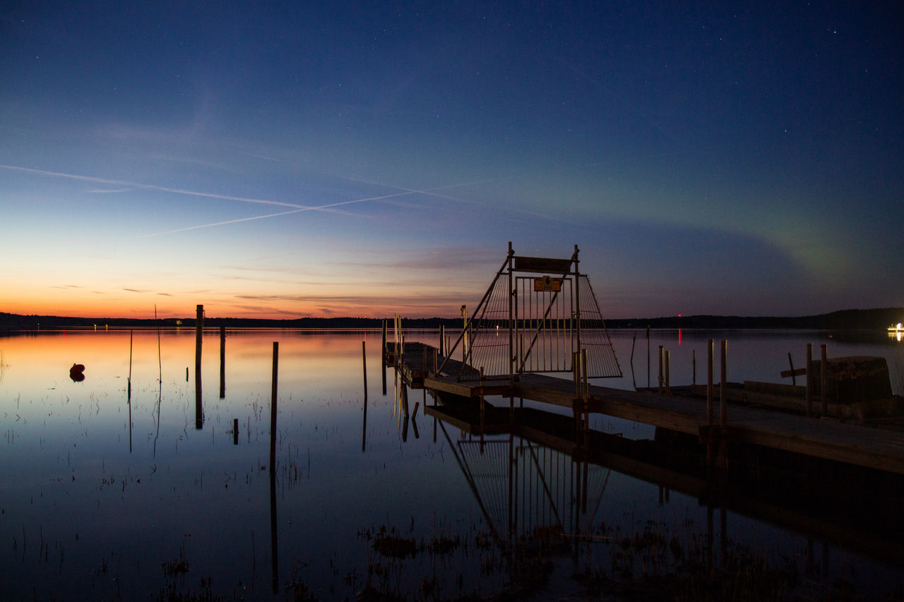 Pier Over Calm Lake Against Blue Sky During Sunset