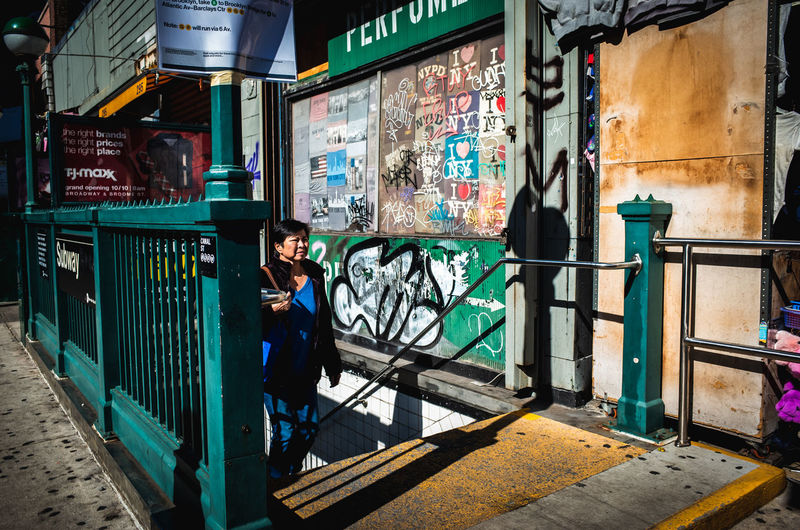 Full length of man standing by graffiti in city
