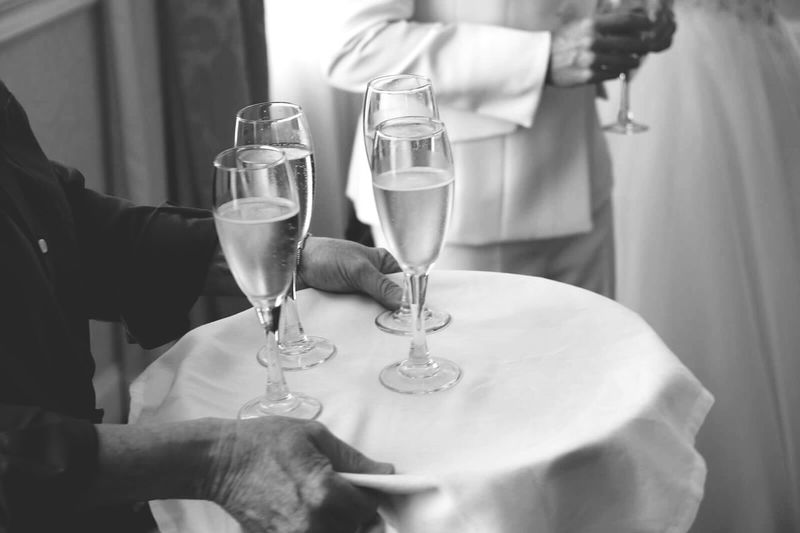 Midsection Of Waiter Holding Champagne Flutes On Tray