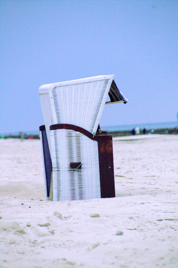 Hooded Chair At Beach Against Clear Sky