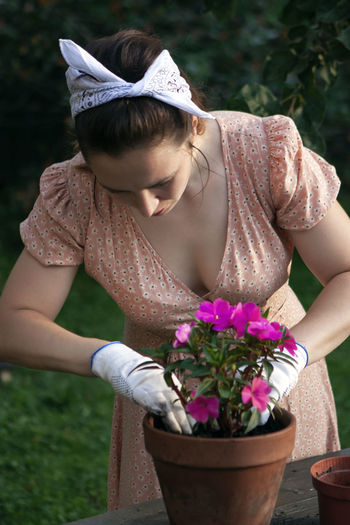A woman replants an impatiens in a new pot