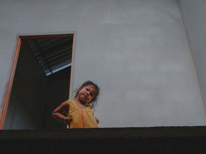 Portrait of smiling girl standing against wall