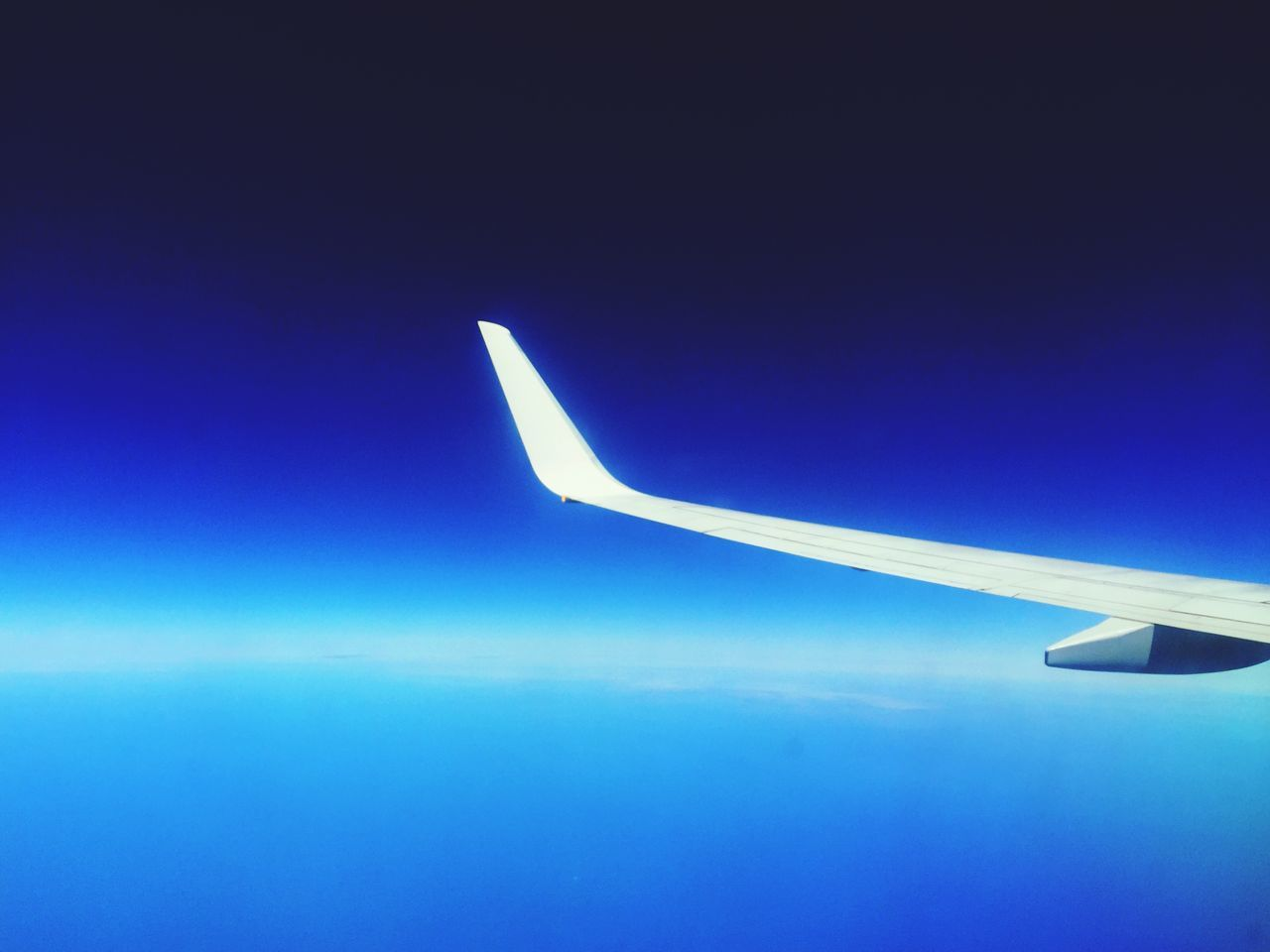 Cropped Airplane Flying In Clear Blue Sky