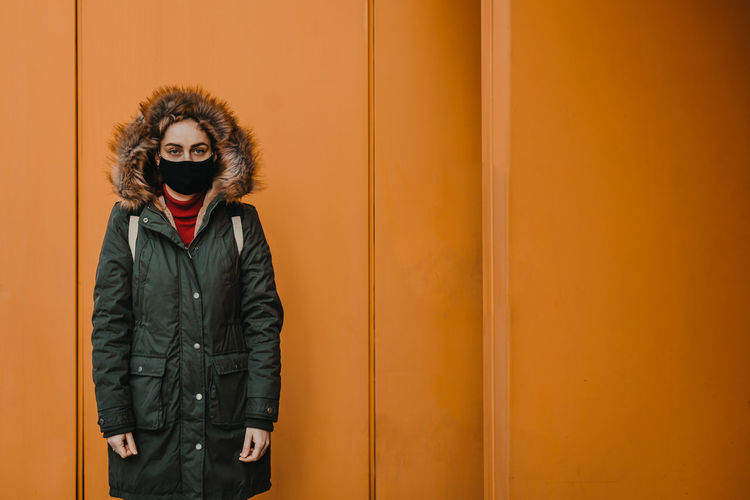 Portrait of young woman wearing mask standing against yellow wall