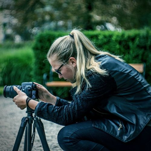 Side view of female photographer adjusting camera