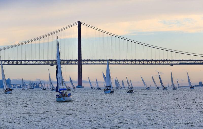 April 25th bridge over boats sailing in sea against sky