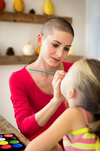 Close-up of mother applying face paint on daughters face at home