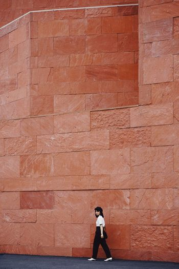 Side view of woman standing against brick wall