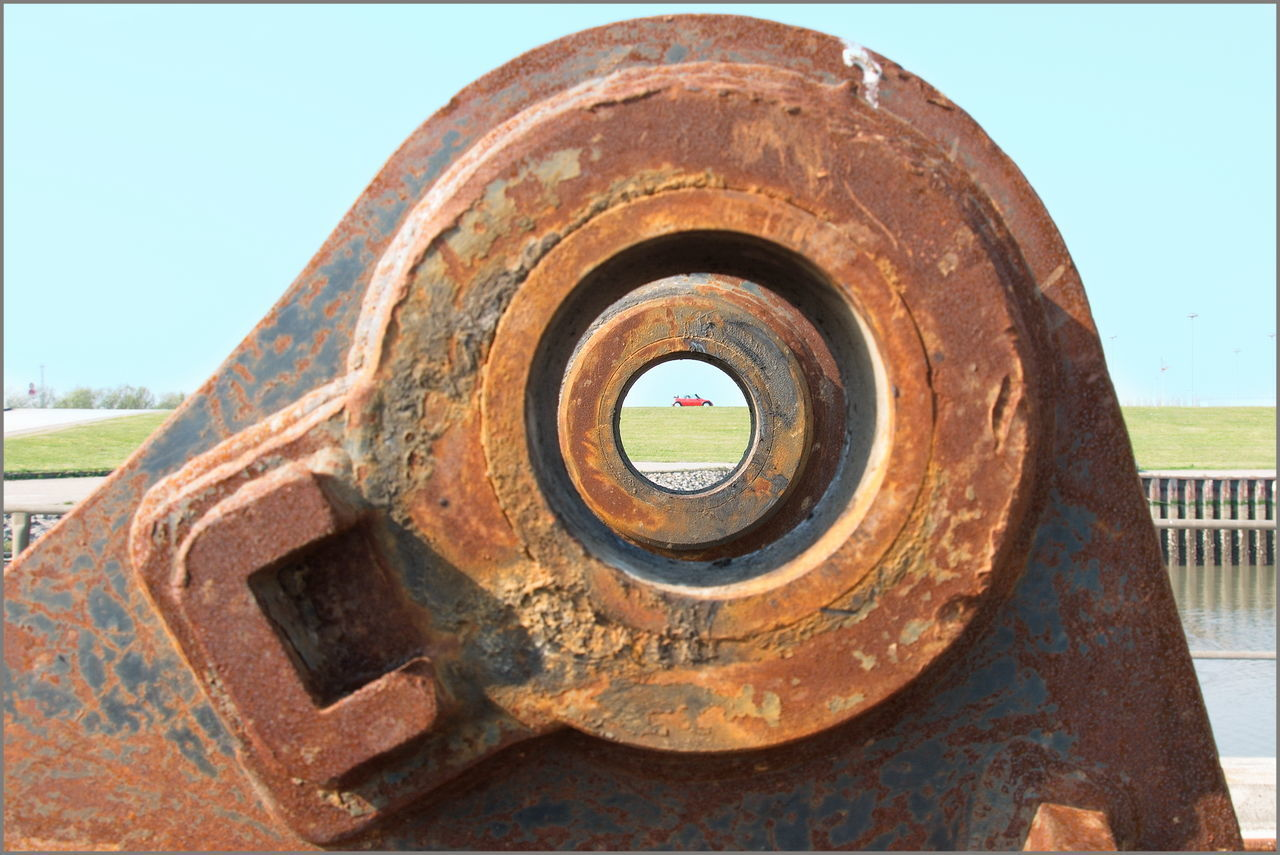 CLOSE-UP OF OLD RUSTY WHEEL AGAINST CLEAR SKY
