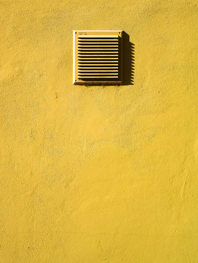 Yellow plaster wall with metal air vent grill Air Conditioner Air Duct Architecture Building Exterior Built Structure Close-up Day Exhaust Fan Metal Grate No People Outdoors Security Bar Square Wall - Building Feature Window Yellow