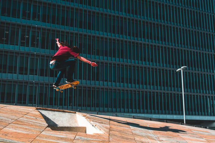 Low Angle View Of Man Skateboarding In Mid-Air Against Building