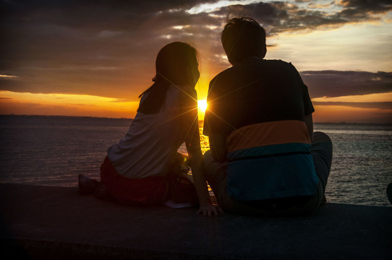 Rear view of couple sitting by sea against sky during sunset