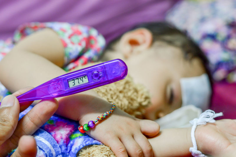 Sick baby lying measuring electric thermometer Child Childhood Holding Women Real People Lifestyles Human Hand One Person Hand Lying Down Indoors  Furniture Girls Wireless Technology Human Body Part Bed Focus On Foreground Close-up Mobile Phone Innocence Themometer Sick