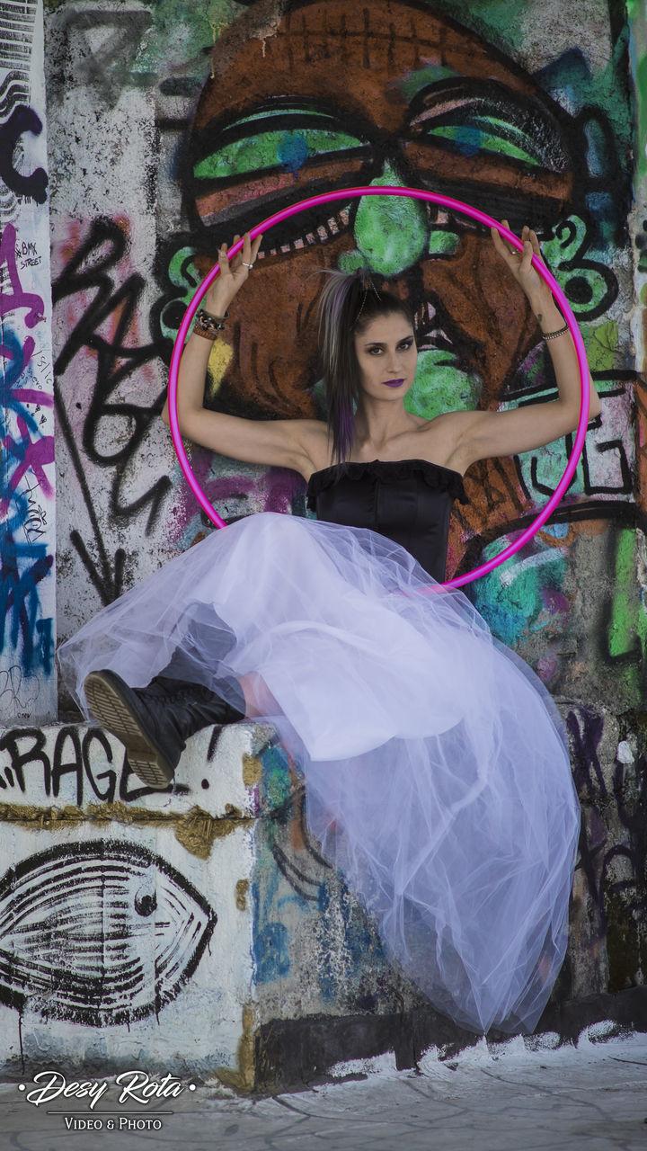 PORTRAIT OF BEAUTIFUL YOUNG WOMAN STANDING ON GRAFFITI