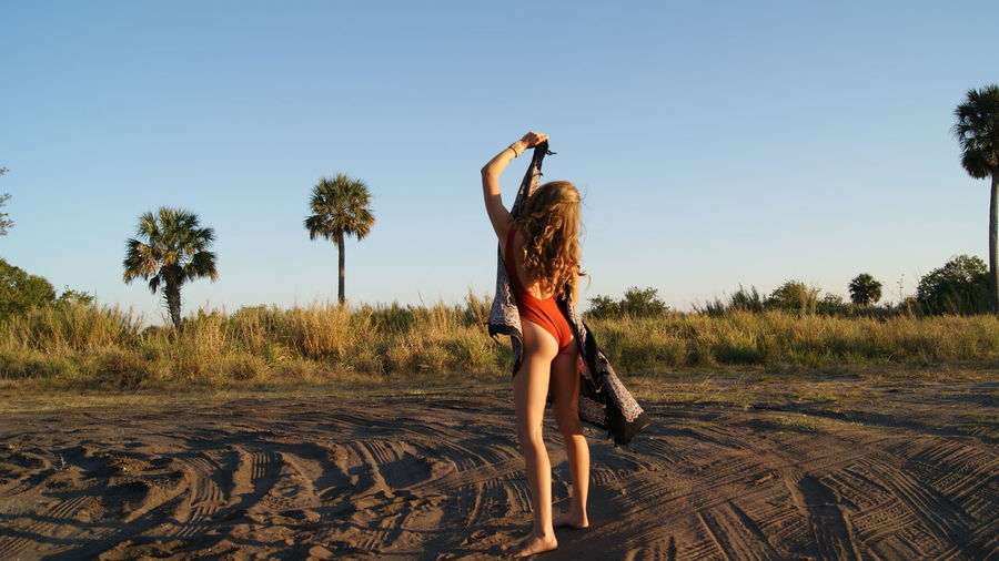 Rear view full length of young woman wearing one piece swimsuit holding scarf on sand