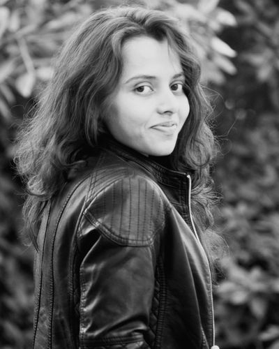 Portrait of smiling young woman wearing leather jacket standing against plants