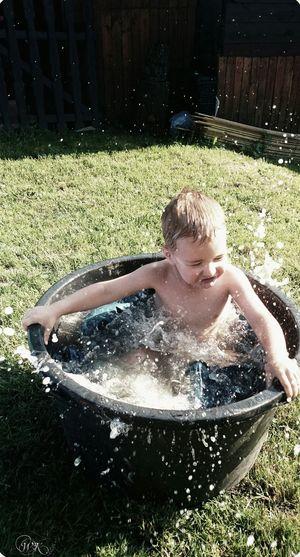 High Angle View Of Toddler Splashing Water While Bathing In Tub At Yard
