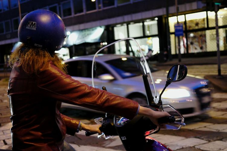 Woman riding motorcycle on city street at night
