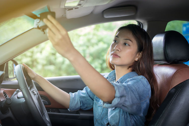 Woman adjusting rear-view mirror while sitting in car