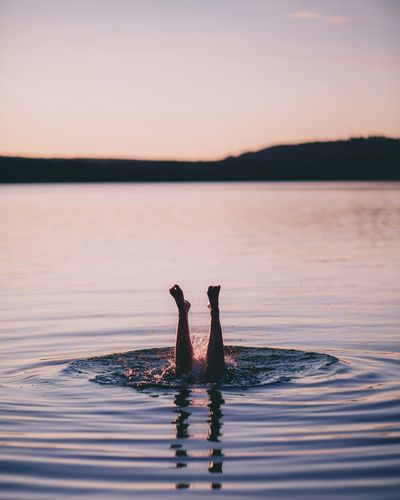 Low section of young woman swimming in lake against sky at sunset