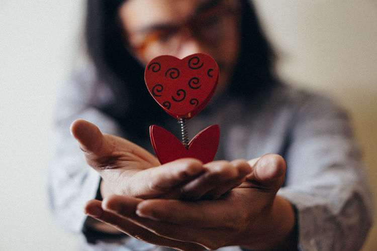 Close-up of mid adult man holding heart shape decoration at home