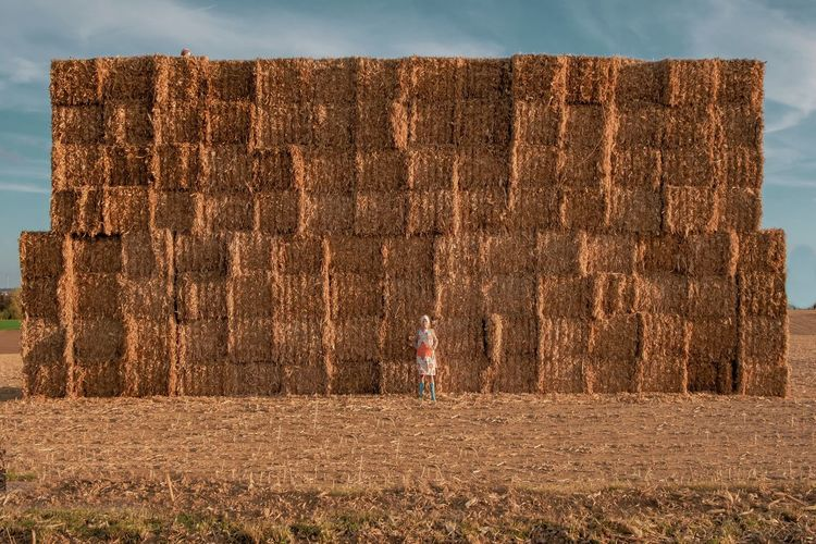 Mid Adult Woman Standing Against Hay Bales