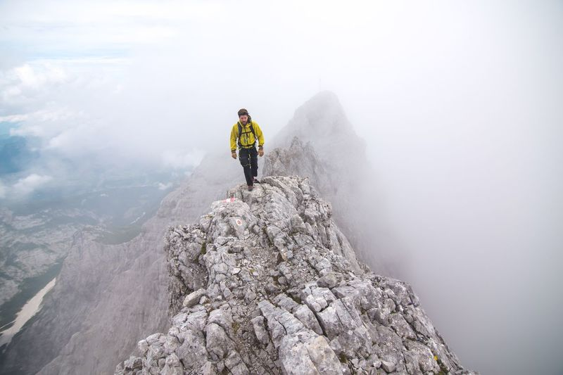 View Of Man Hiking On Mountain Peak