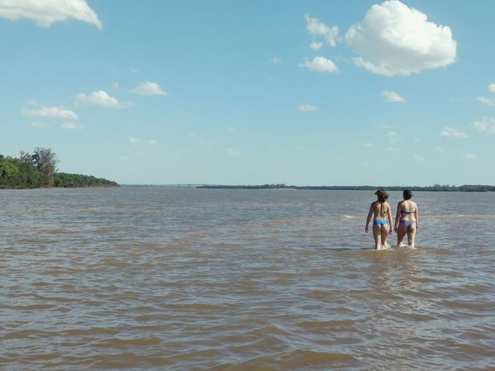 Rear view of young women walking in sea against sky