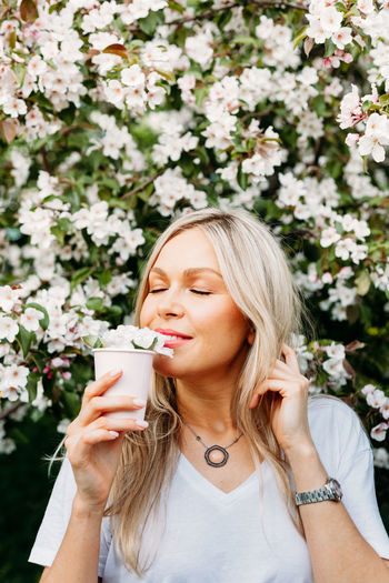 Woman with eyes closed holding cup by flowering plants