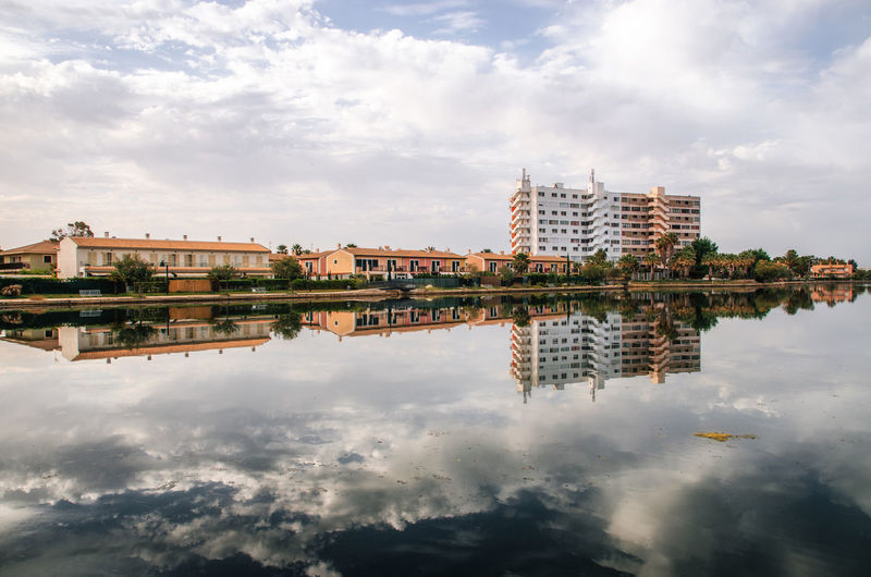 Reflection of buildings and cloudy sky on esperanza lake